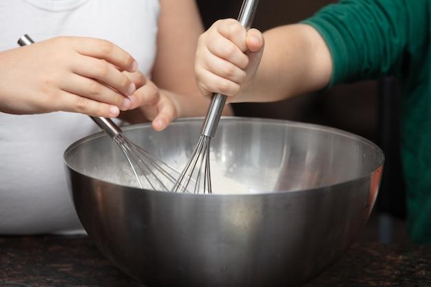 母と子がボウルの中でケーキの材料を混ぜる