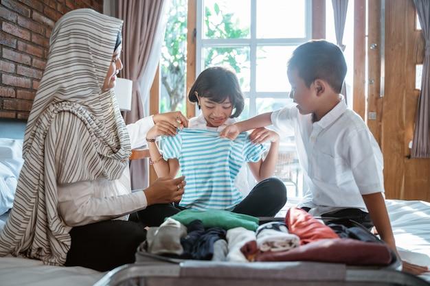 母親と子供は服を準備し、スーツケースに入れます