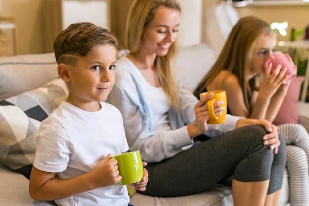 Мать и ее дети пьют из чашек