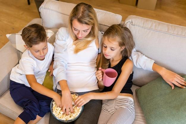 母と彼女の子供たちが販売ボウルからポップコーンを食べる
