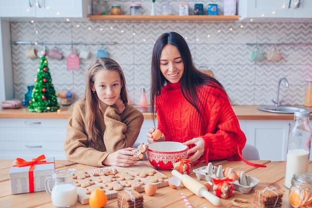 母と彼女のかわいい娘がクッキーを調理します
