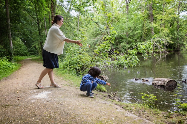 公園の池でアヒルに餌をやる母と彼女のかわいい小さな子供。家族のレジャー