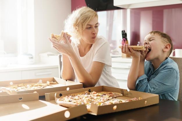 Мать и ее милый сын едят вкусную итальянскую пиццу дома