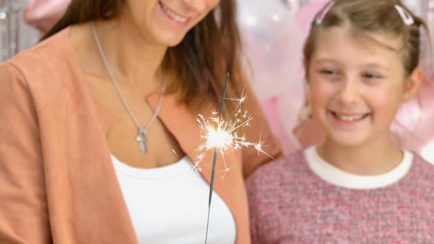 母と彼女の娘は誕生日パーティーで線香花火が燃えるのを見ています