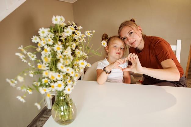 어머니와 그녀의 딸은 그들의 손으로 사랑의 상징을 보이고있다.