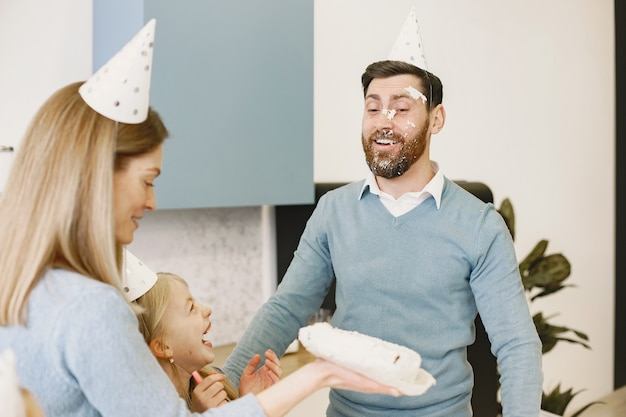 어머니와 그녀의 딸은 부엌에서 아버지의 생일을 축하합니다 어머니는 망 얼굴에 케이크를 안타