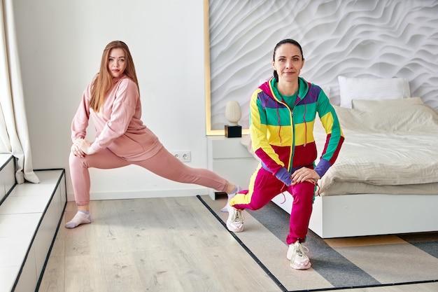 Мать и ее дочь делают упражнения на растяжку