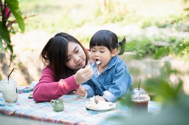 어머니와 그녀의 딸 카페에서 케이크를 먹고
