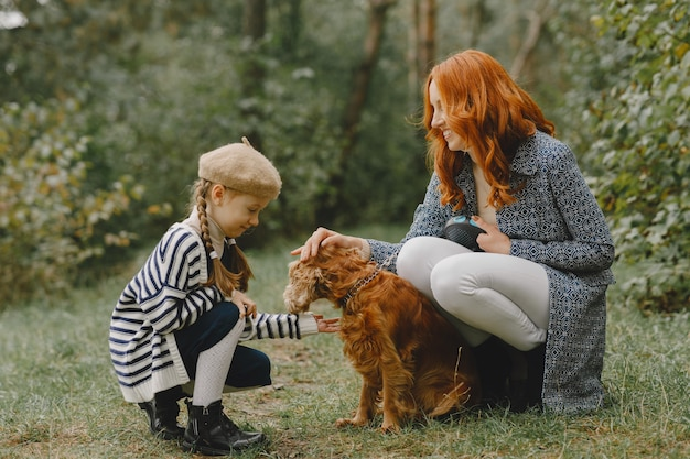 犬と遊ぶ母と娘。秋の公園の家族。ペット、家畜、ライフスタイルのコンセプト。秋の時間。