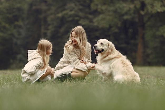 犬と遊ぶ母と娘。秋の公園の家族。ペット、家畜、ライフスタイルのコンセプト