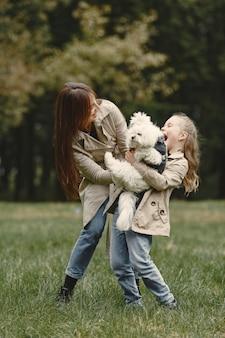 엄마와 강아지와 함께 연주 그녀의 딸입니다. 가을 공원에서 가족. 애완 동물, 가축 및 생활 양식 개념