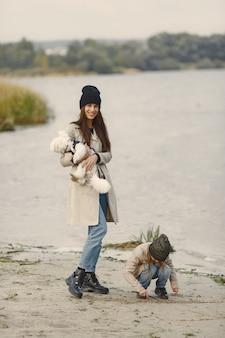 Мать и ее дочь играют с собакой. концепция домашних животных, домашних животных и образа жизни