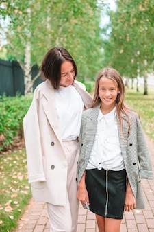 Мать и дочь в школу. очаровательные маленькие девочки очень рады вернуться в школу