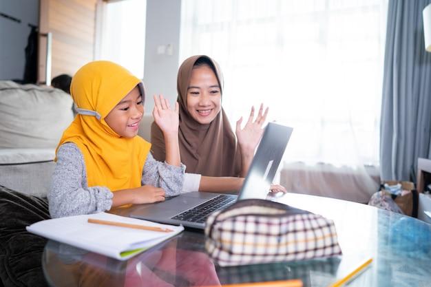 母と娘は、自宅から学校とのクラスミーティング中にラップトップコンピューターに手を振る