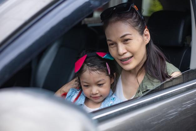 보호용 의료 마스크를 쓴 엄마와 딸이 차에 앉아 있습니다.