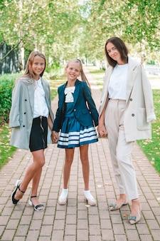 Мать с дочерьми в школу. очаровательные маленькие девочки очень рады вернуться в школу