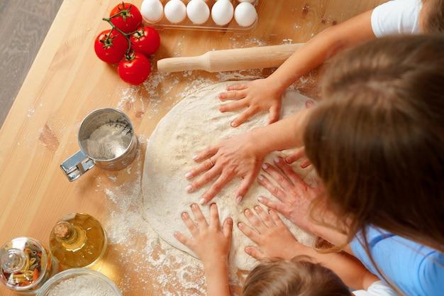 Мать и ее дети замешивают тесто на кухонном столе