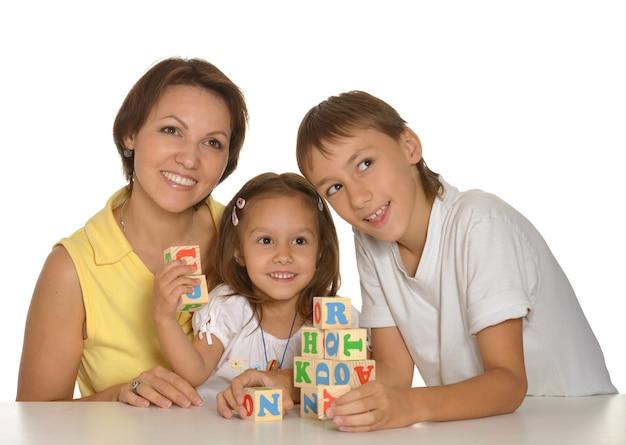 흰색으로 격리된 큐브를 가지고 노는 엄마와 아이들