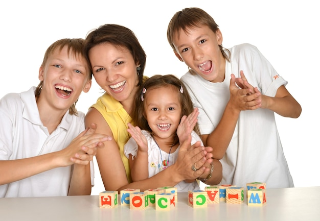 Мать и ее дети играют с кубиками, изолированными на белом