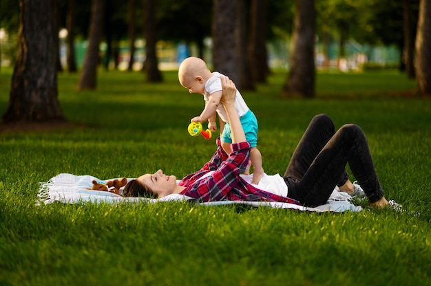 어머니와 그녀의 작은 아기 여름 공원에서 잔디에 누워