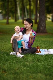 어머니와 그녀의 작은 아기 여름 공원에서 잔디에 포즈
