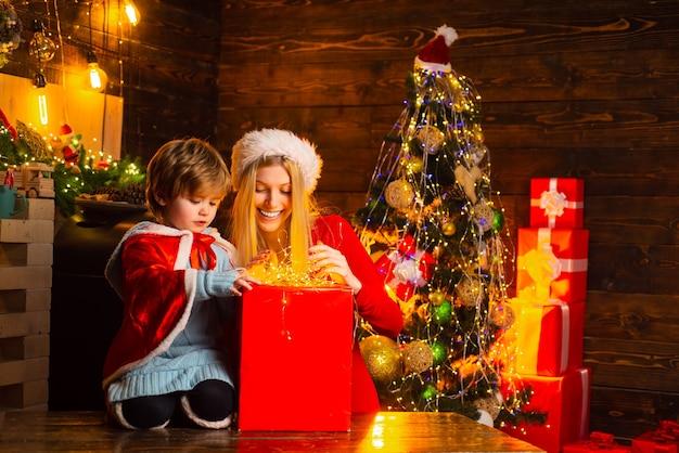 プレゼントのギフトボックスとクリスマスライトを持っている母と彼女の小さな男の子は、新年あけましておめでとうございますクリスマスツリーハプ...