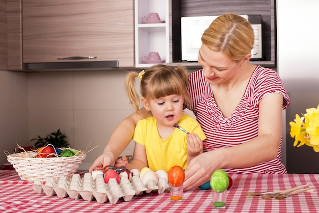 Мать и ее маленький ребенок рисуют пасхальные яйца
