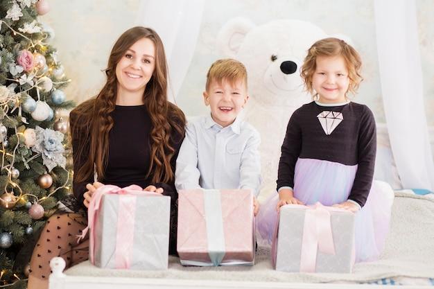 母と彼女の小さな子供たちとクリスマスギフトボックス