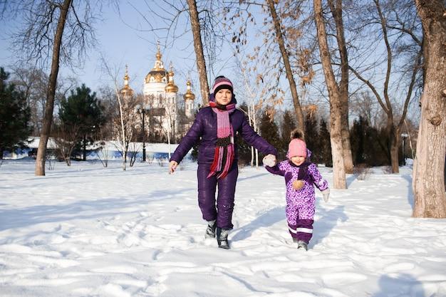 어머니와 그녀의 작은 딸 아름 다운 겨울 날 야외에서 즐기는.