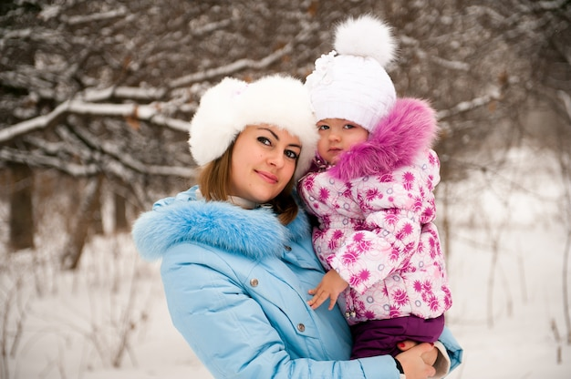 Мать и ее маленькая дочь, наслаждаясь красивый зимний день.