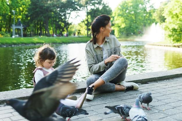 Мать и ее маленькая дочь кормит птиц в городском парке
