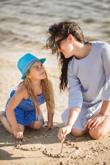 母と海岸で楽しんでいる彼女の小さな娘。若い可愛いママと彼女の子供は水の近くで遊んで、砂の上の心を描く