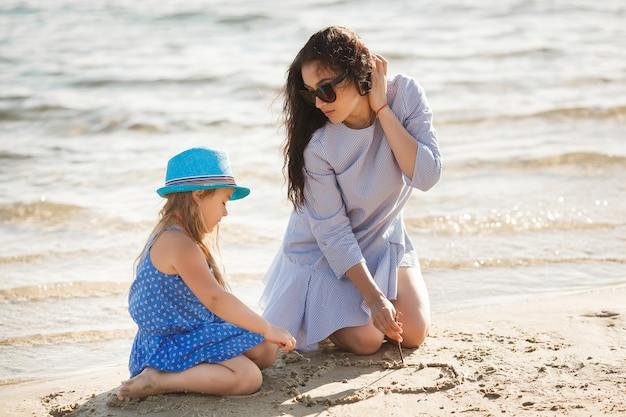母と彼女の小さな娘が海岸で楽しんでいます。若い可愛いお母さんと彼女の子供が水の近くで遊んで、砂の上にハートを描く