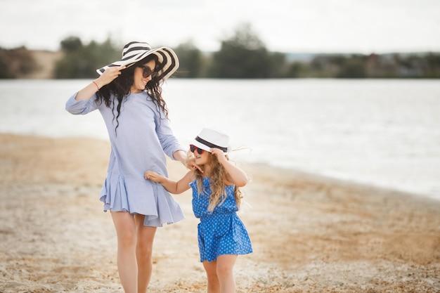 母と海岸で楽しんでいる彼女の小さな娘。若いかわいいママと彼女の子供が水の近くで遊んで