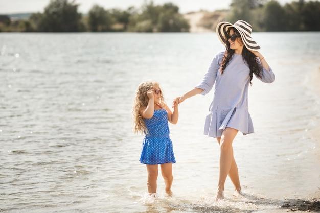母と彼女の小さな娘が海岸で楽しんでいます。若い可愛いお母さんと彼女の子供が水の近くで遊んで
