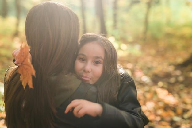 가 시즌에 가을 공원에서 어머니와 그녀의 작은 딸.