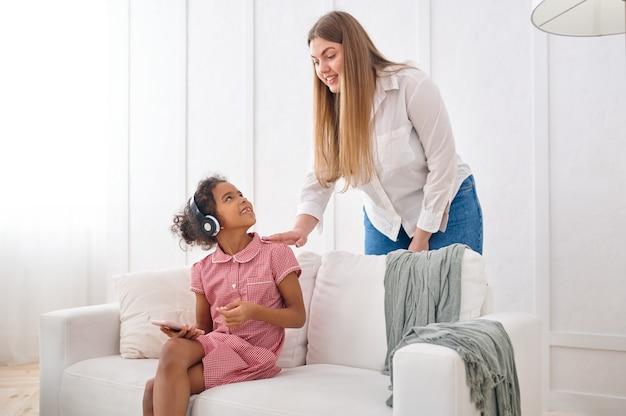 거실 소파에 헤드폰을 끼고 있는 어머니와 어린 딸. 엄마와 여자 아이는 함께 집에서 여가를 즐기고, 좋은 관계, 부모의 보살핌