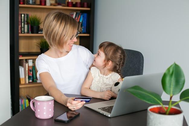Мать и ее маленькая дочь смотрят друг на друга во время покупок в интернете