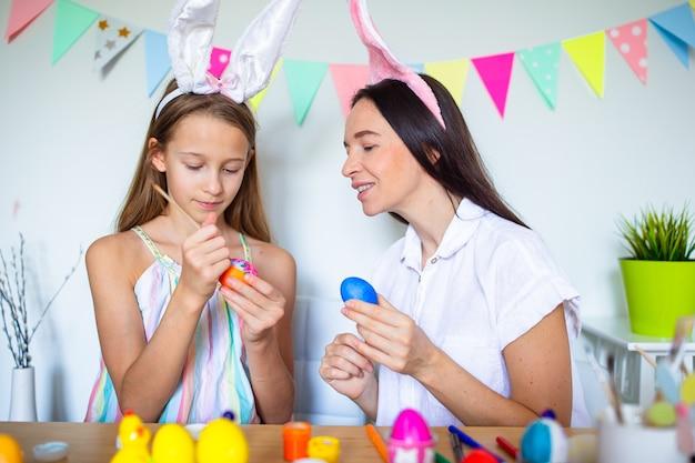 어머니와 그녀의 작은 딸 그림 계란 행복한 가족 부활절 준비
