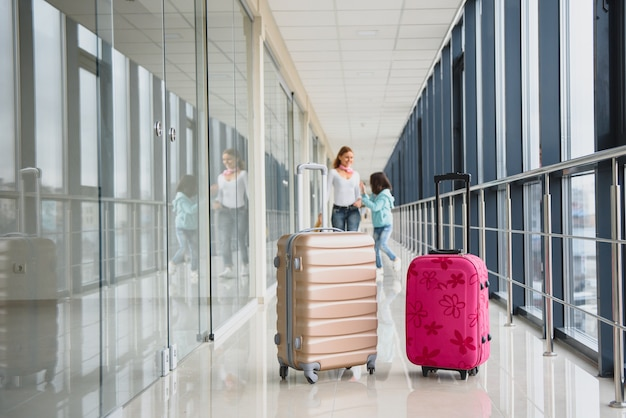 母と空港で荷物を持って彼女の小さな娘