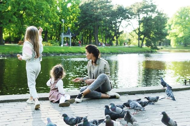 Мать и ее маленькие дочери кормят птиц в городском парке