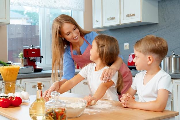 Мать и ее маленькие дети, мальчик и девочка, помогают ей готовить тесто