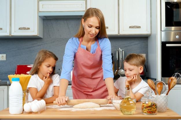 母と彼女の小さな子供たち、男の子と女の子、彼女が生地を準備するのを助ける