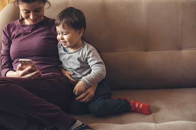 어머니와 그녀의 작은 아들이 소파에 앉아 함께 시간을 보내는 전화에 미소