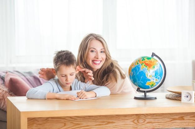 Мать и ее маленький сын решили проблему. молодая мама и ее ребенок делают домашнее задание