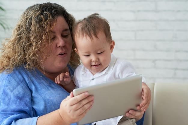 コロナウイルスのパンデミックのために家にいるときにタブレットコンピューターでアニメを見ている母と彼女の幼い息子