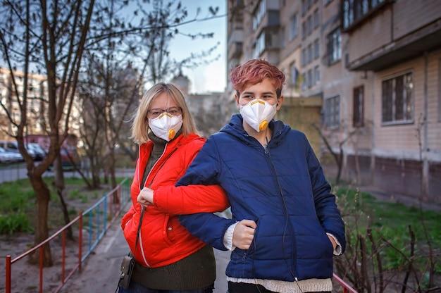 새로운 규칙으로 서로 인사하는 인공 호흡기를 착용 한 어머니와 밀레 니얼 세대 딸