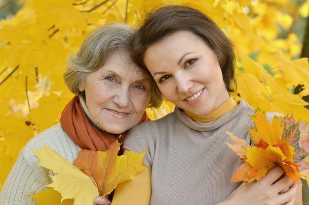 秋の公園で母と彼女の素敵な娘