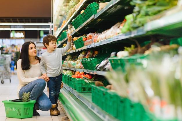 Мать и ее сын покупают фрукты на фермерском рынке