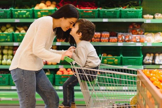 농민 시장에서 과일을 사는 어머니와 그녀의 아들
